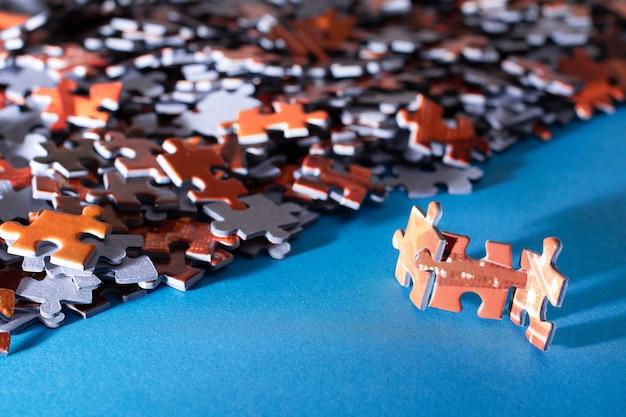 Gemengde stukken van een kleurrijke legpuzzel liggen op de blauwe achtergrondstrategie en het oplossen van problemen...