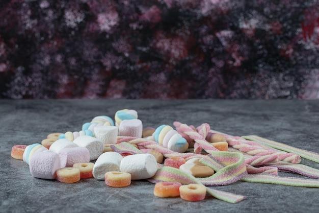 Gemengde vorm marshmallows en jellybeans op marmer.