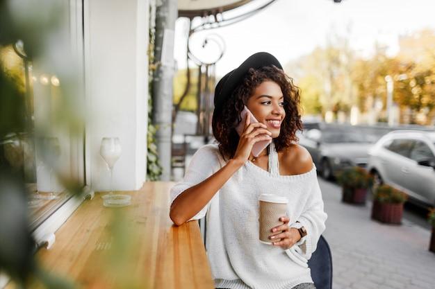 Gemengde vrouw met afrokapsel dat door mobiele telefoon spreekt en op stedelijke achtergrond glimlacht. zwart meisje dat vrijetijdskleding draagt. kopje koffie te houden. zwarte hoed.