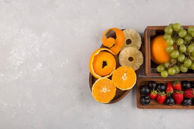 Gemengde vruchten en bessen in houten schotels op witte ruimte