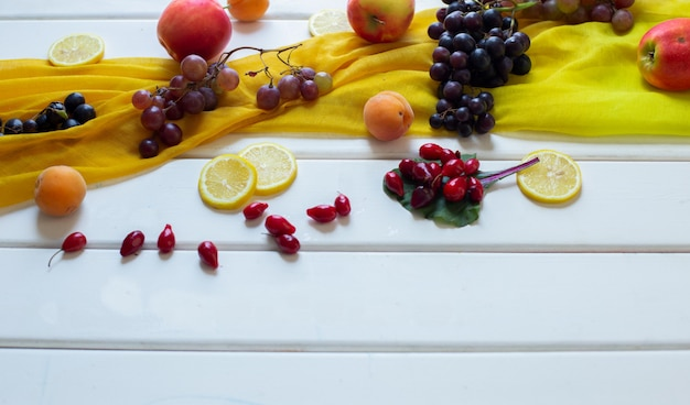 Gemengde vruchten op een gele sjaal op een witte tafel, hoekmening.