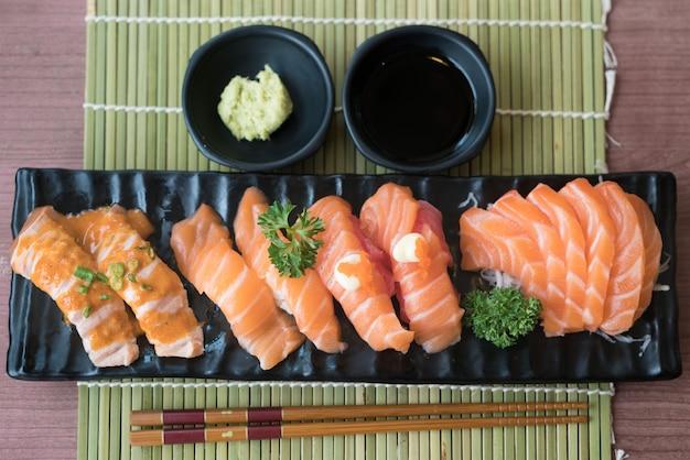 Gemengde zalmsushi op zwarte plaat samen met japanse saus en groene bladdecoratie,