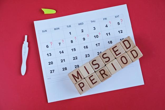 Gemiste periode gemarkeerd op kalender, zwangerschapstest. gezondheid van de vrouw en vertraging in de menstruatie.
