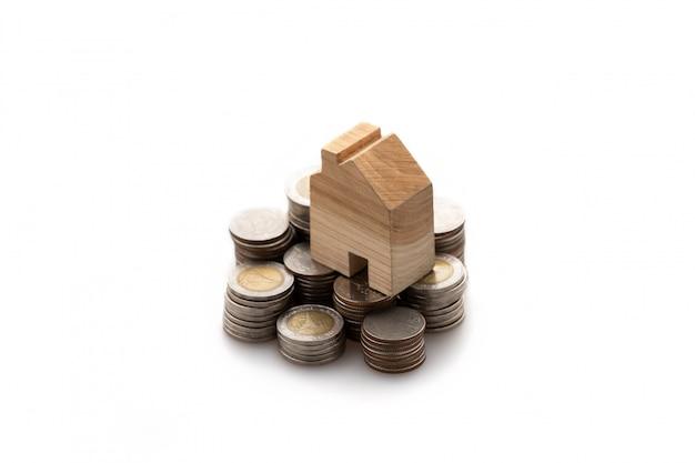 Gemodelleerd houten huis geplaatst op een stapel munten