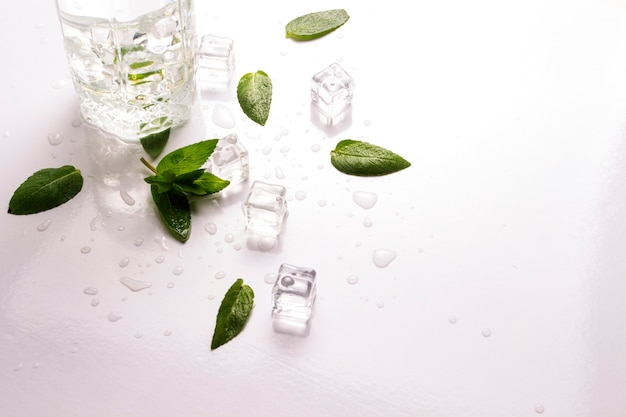 Gemorst glas met verfrissend water, muntblaadjes en ijsblokjes op een witte ondergrond. platliggend, bovenaanzicht