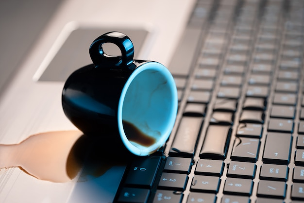 Gemorste koffie of thee op een laptop. uitzicht van boven