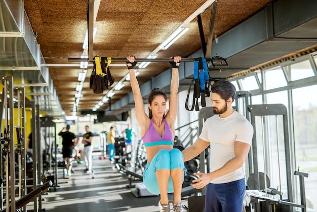 Gemotiveerd en gefocust aantrekkelijk donkerbruin jong fitnessmeisje die abs-oefeningen op de balk hierboven doen terwijl ze de benen opheft met een personal trainer naast haar.