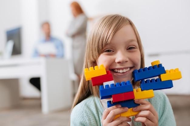 Gemotiveerd intelligent oprecht meisje dat mooie figuren maakt met behulp van plastic puzzelstukjes