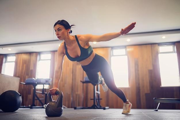Gemotiveerd meisje dat plankoefening doet die kettlebells met één hand gebruiken bij gymnastiek, volledige lengtefoto, exemplaarruimte