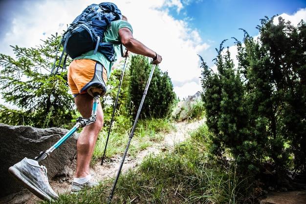 Gemotiveerde actieve mannelijke toerist met prothese die omhoog gaat tijdens het proberen van nordic walking