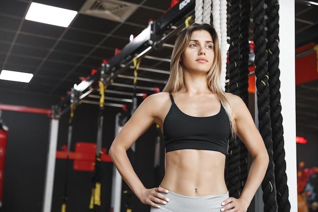Gemotiveerde atletische sportvrouw in activewear-beha, zelfverzekerde handen op de heupen.