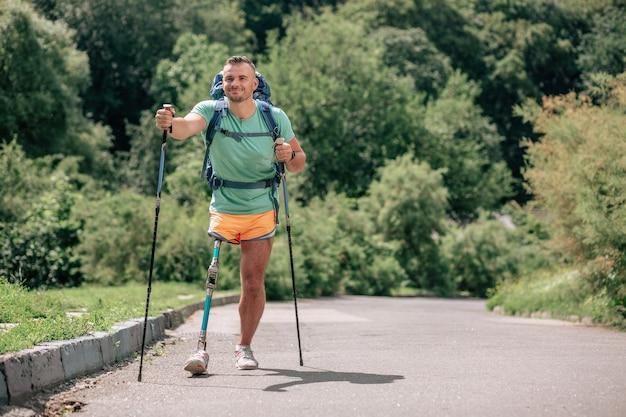 Gemotiveerde enthousiaste man die aan nordic walking doet terwijl hij geniet van frisse lucht