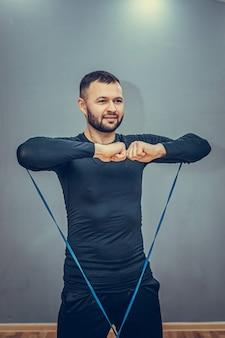 Gemotiveerde, goed uitziende sporter doet squats met weerstandstouw