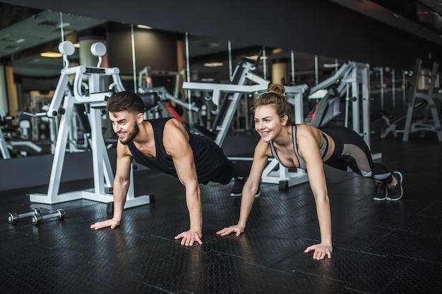 Gemotiveerde jonge blonde vrouw en man in het midden van de training, staande in de plank met de handen tegen elkaar gebald.