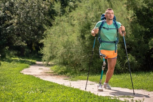 Gemotiveerde jonge man die lijdt aan verlamming tijdens het proberen van nordic walking