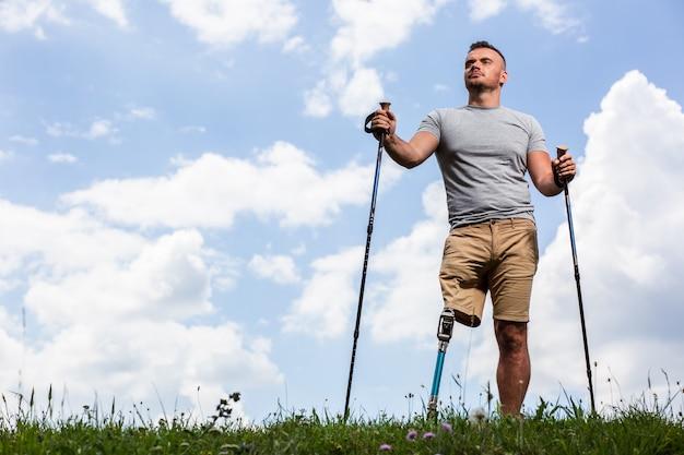 Gemotiveerde jonge man die nordic walking probeert terwijl hij geniet van mooi weer