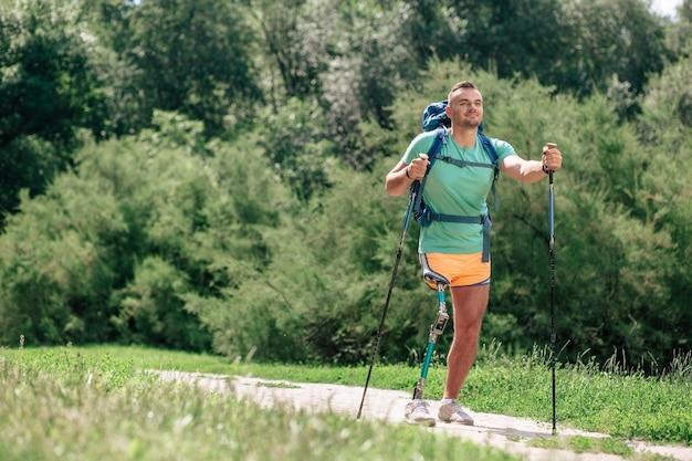 Gemotiveerde jonge man met prothese die nordic walking probeert terwijl hij geniet van sportactiviteiten