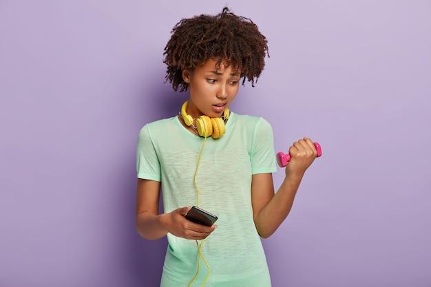 Gemotiveerde jonge vrouw met afro-kapsel, heeft moeilijke oefeningen met halter, heft gewicht op