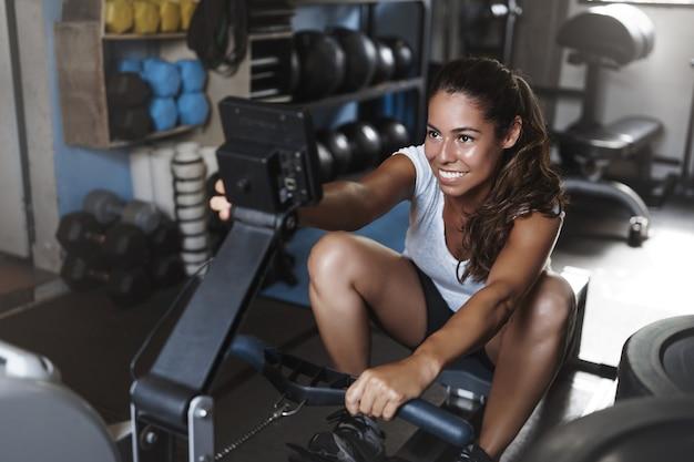 Gemotiveerde jonge vrouwelijke atleet, glimlachend in de sportschool, met behulp van beenpress-apparatuur