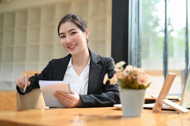 Gemotiveerde jonge zakenvrouw handen holdind notitie boek zittend in haar kantoor.