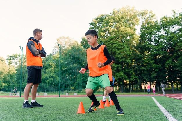 Gemotiveerde jongens in oranje vesten rennen tussen de plastic kegels tijdens voetbaltraining in het stadion.