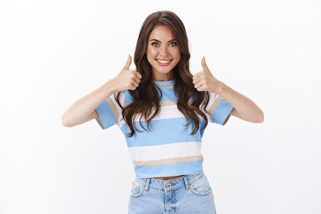 Gemotiveerde, knappe, gelukkige jonge vrouw ondersteunt en accepteert een geweldig idee, laat de duim omhoog lachend jureren, beveelt een product van goede kwaliteit aan, accepteert en keurt uitstekende service goed