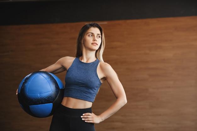Gemotiveerde knappe sportvrouw in sportkleding, met medicijnbal op taille en hand op heup.