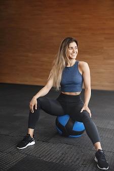 Gemotiveerde knappe sportvrouw in sportkleding, zittend op de bal.