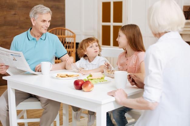 Gemotiveerde levendige, mooie familiebijeenkomst aan tafel en het eten van een ochtendmaaltijd terwijl ze hun plannen voor vandaag bespraken