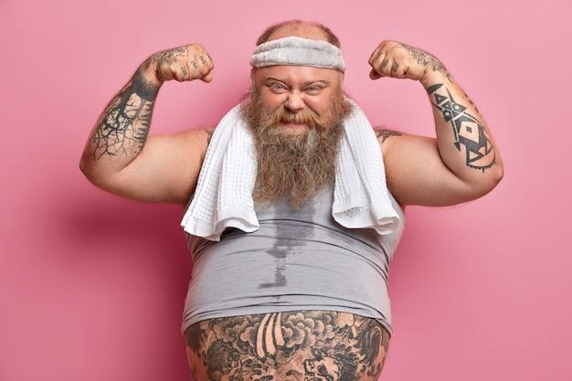 Gemotiveerde man met overgewicht met baard heft armen op, toont spieren na training, wil sterk zijn en biceps hebben, leidt een gezonde levensstijl, heeft fitnessprogramma voor gewichtsverlies, vertrouwen in zichzelf.