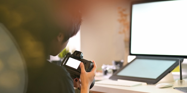 Gemotiveerde mannelijke fotograaf die zijn camera controleert