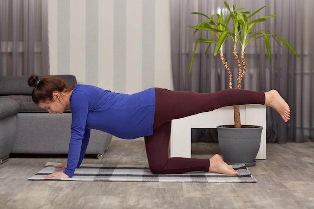 Gemotiveerde mooie aanstaande moeder draagt vrijetijdskleding, strekt haar benen, doet ochtendoefeningen, poseert alleen in een modern appartement en toont een goede flexibiliteit.