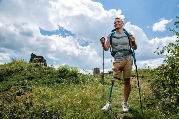 Gemotiveerde positieve man met lichamelijke aandoeningen die nordic walking probeert tijdens een actief weekend