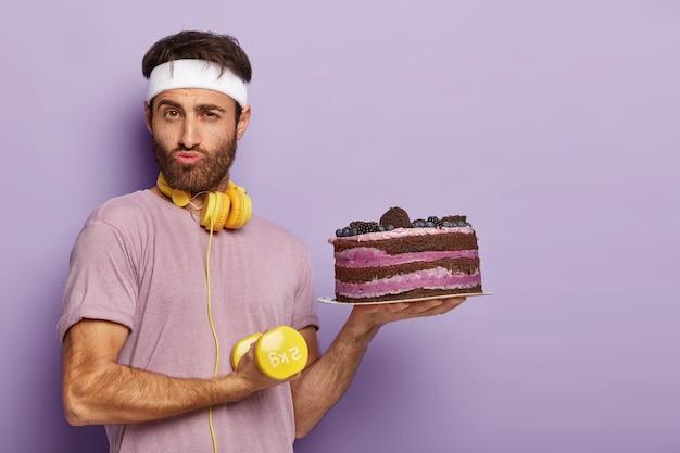 Gemotiveerde serieuze man heeft sterke biceps, houdt gele halters, leidt een gezonde levensstijl, houdt vers gebakken cake vast