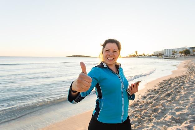 Gemotiveerde sportieve vrouw die duimen op succesgebaar doet na stedelijke training aan de kust.