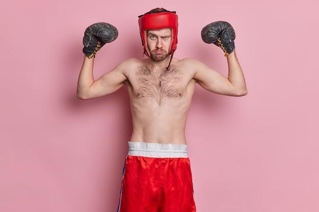 Gemotiveerde sportman houdt van boksen draagt beschermende hoed handschoenen armen omhoog armen toont spieren heeft mager lichaam staat met blote romp ziet er serieus uit.