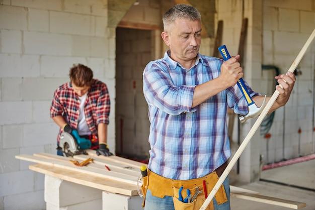 Gemotiveerde timmerman die hamer gebruikt in het hoofdplan