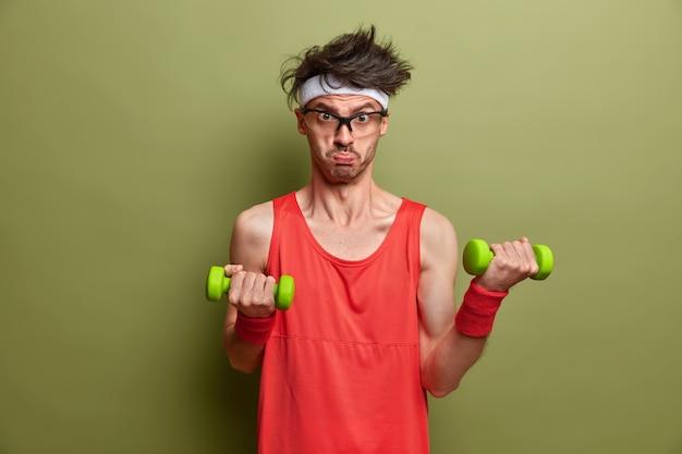 Gemotiveerde vastberaden sportman leidt sportieve levensstijl, heft zware halters op voor spiertraining, doet ochtendfitness thuis, wil biceps, draagt rood shirt en polsbandje, ziet er droevig uit