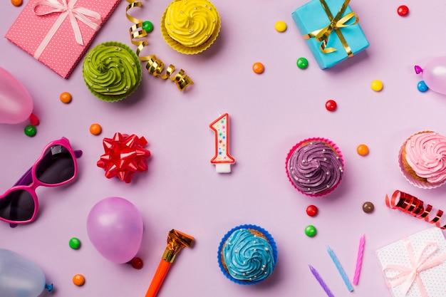 Gems; strik; lint; zonnebril; ballon; muffins op roze achtergrond