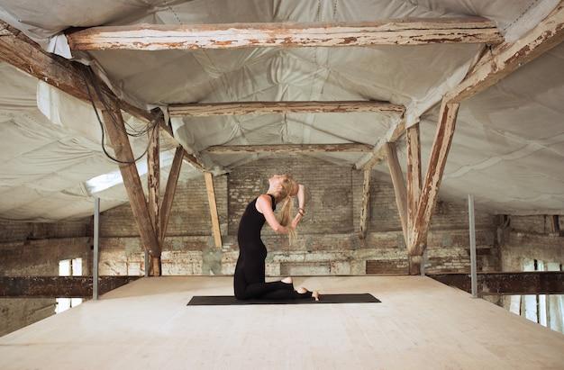 Genade. een jonge atletische vrouw oefent yoga op een verlaten bouwgebouw. geestelijke en lichamelijke gezondheid. concept van een gezonde levensstijl, sport, activiteit, gewichtsverlies, concentratie.