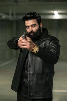Genadeloze bebaarde huurmoordenaar of terrorist in zwart leren jasje die pistool op slachtoffer of rivaal richt voordat hij schiet