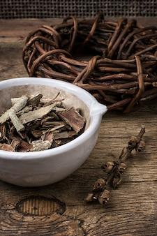 Geneeskrachtige zoethout gerold in spoel en esp schors op houten achtergrond.