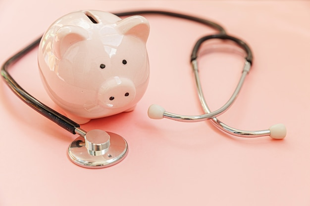 Geneeskunde arts apparatuur stethoscoop en spaarvarken geïsoleerd op roze pastel achtergrond. gezondheidszorg financiële controle of besparing voor het concept van medische verzekeringskosten. kopieer ruimte.
