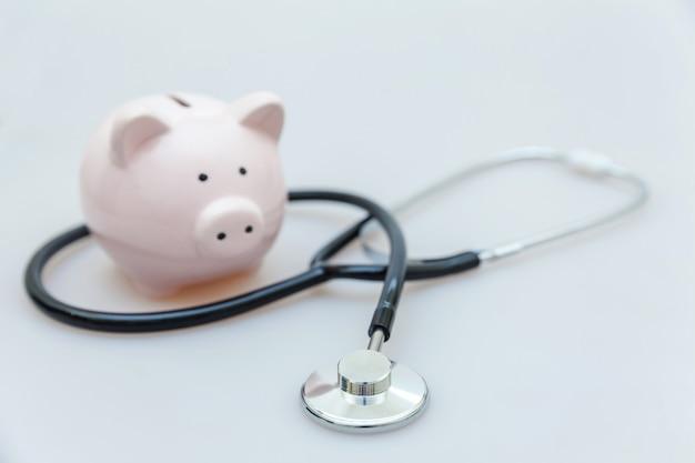 Geneeskunde arts apparatuur stethoscoop of phonendoscope en spaarvarken op wit wordt geïsoleerd