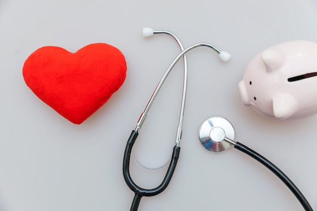Geneeskunde arts apparatuur stethoscoop of phonendoscope spaarvarken en rood hart geïsoleerd op wit