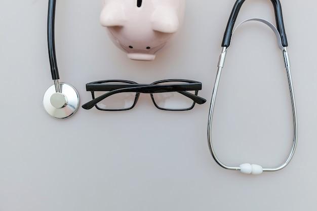 Geneeskunde arts apparatuur stethoscoop spaarvarken bril op witte achtergrond