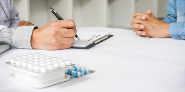 Geneeskunde arts hand met pak van verschillende tablet blaren voor de patiënt