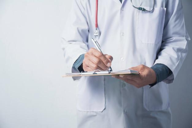 Geneeskunde arts met stethoscoop en holdingsaanvraagformulier op wit.