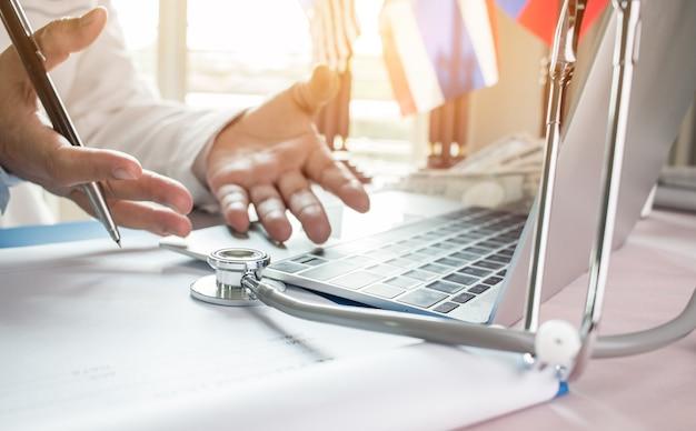 Geneeskunde artshand die voor patiënt bij het raadplegen van ruimte verklaren die aan laptop werken