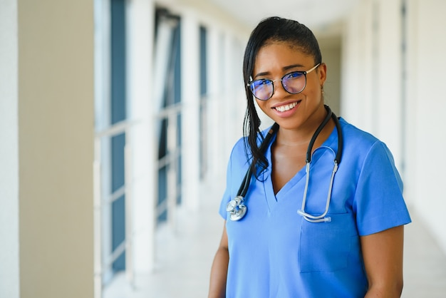 Geneeskunde, beroep en gezondheidszorg concept - gelukkig lachende afro-amerikaanse vrouwelijke arts met stethoscoop over ziekenhuis achtergrond